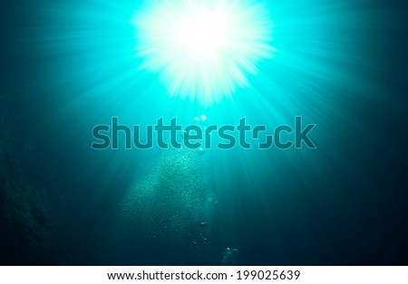 Rising bubbles and sun rays in green coloured water
