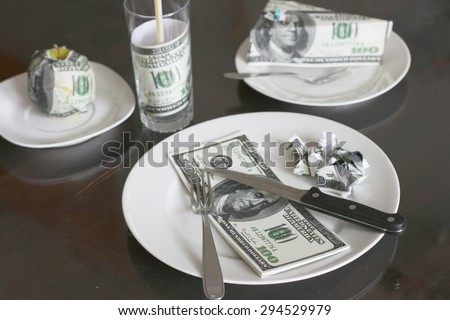 Rising food prices, high cost of living concept, eating foot made out of money - fake 100 dollar bills - stock photo