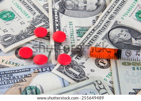 Rising healthcare expenses - pills and syringe on dollar bills - stock photo