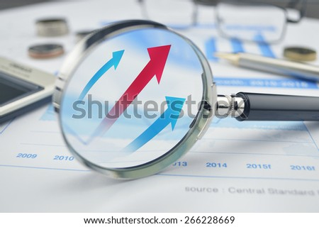 Rising red and blue arrow on magnifying glass, success concept - stock photo