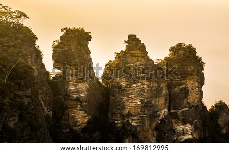Rising sun illuminates the Three Sisters rock formation in the valley from Echo Point overlooking the majestic Blue Mountains near Sydney NSW Australia - stock photo