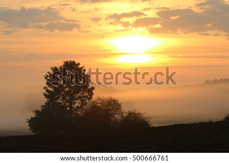Rising sun over rural countryside
