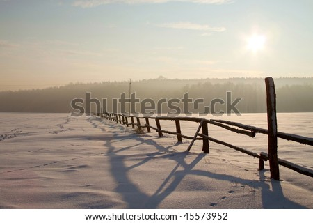 Rising sun over snow covered field with a wooden fence in the foreground. - stock photo