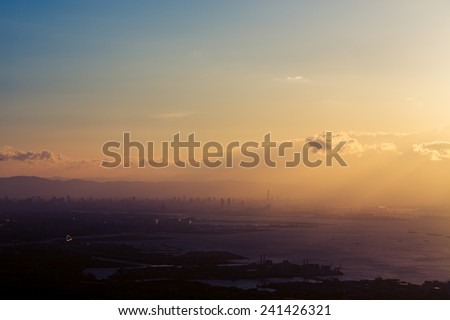 Rising sun shining above city - filtered dramatic look - stock photo