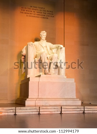 Rising sunrise at dawn lights statue of President Lincoln in memorial in Washington DC - stock photo