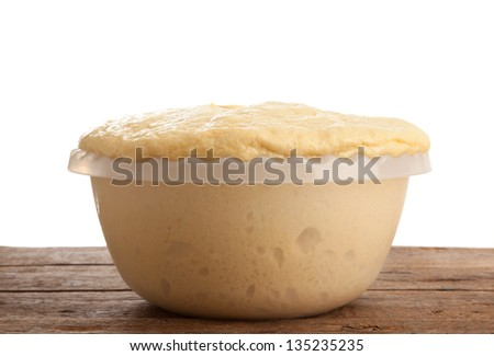 Rising Yeast Dough in bowl on wooden table - stock photo