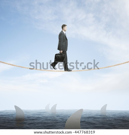 Risk concept with businessman walking on rope above sea full of sharks on sky background