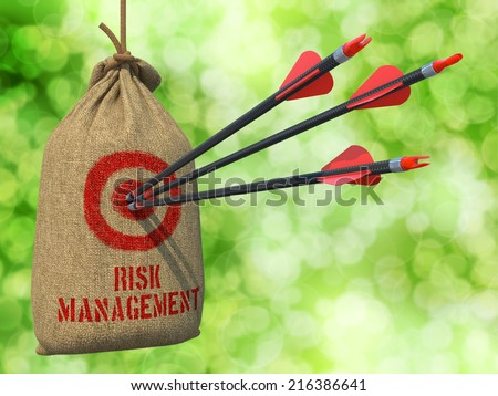 Risk Management - Three Arrows Hit in Red Target on a Hanging Sack on Green Bokeh Background. - stock photo