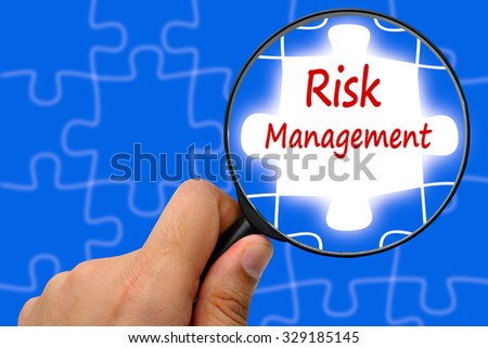 Risk management word. Magnifier and puzzles. - stock photo
