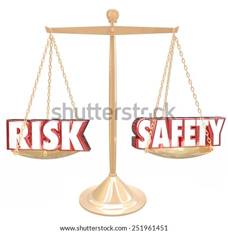 Risk Vs Safety 3d words on a gold scale to illustrate, weigh or compare the differences between two options and their relative danger or warning factors - stock photo