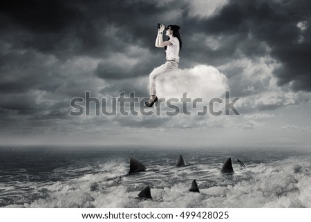 Risky Business concept: Young Asian businesswoman sitting on the cloud and looking through binoculars above dangerous sharks on the sea