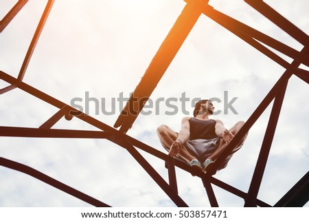 Risky man sitting on high metal construction