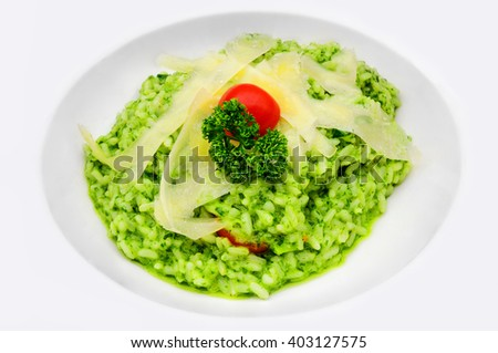Risotto al Pesto with parmesan cheese stripes and cherry tomato, served in a white plate - stock photo