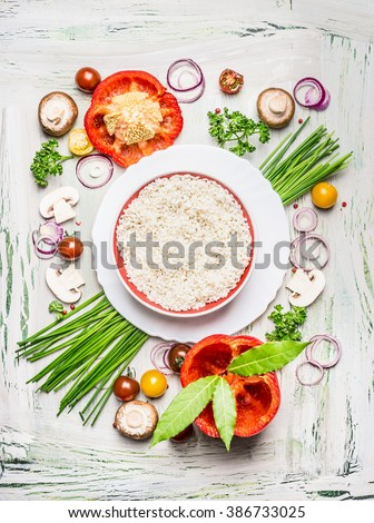 Risotto rice dish  and various vegetables and seasoning ingredients  for tasty vegetarian cooking on light  rustic wooden background, top view composing. Healthy eating and diet food concept.  - stock photo