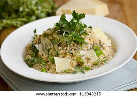 Risotto topped with shaved Parmesan, parsley, chives and thyme