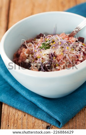 Risotto with beetroot in bowl on wooden table
