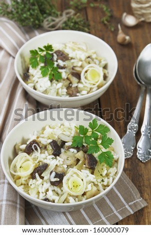 Risotto with mushrooms and leek in a bowl on the table