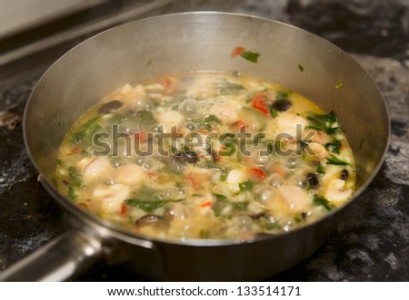 Risotto with mushrooms and vegetables being cooked in pan