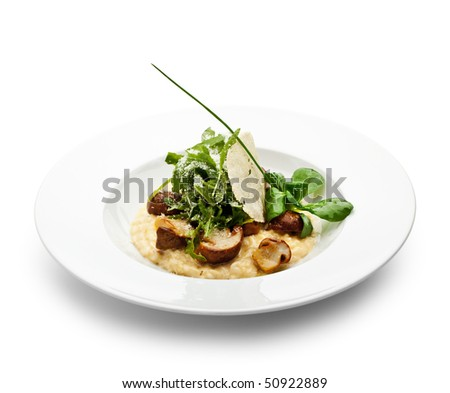 Risotto with Mushrooms, Corn Salad, Rucola and Truffle. Served with Parmesan Chip and Spring Onions - stock photo