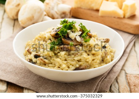 risotto with mushrooms, fresh herbs and parmesan cheese. - stock photo