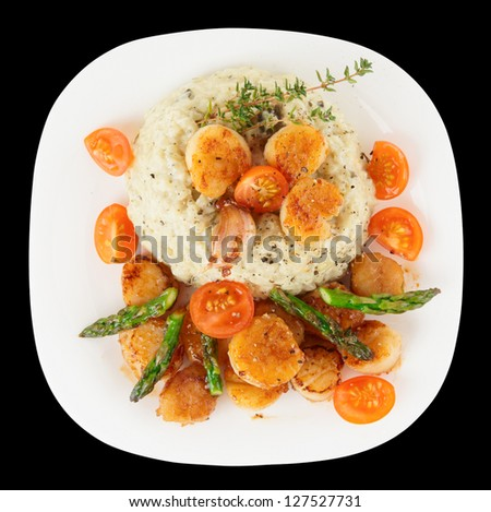 Risotto with pan seared sea scallops isolated on black background - stock photo