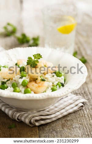 Risotto with pea and shrimps - stock photo