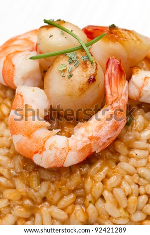 risotto with seafood sauce with scallops and prawns - stock photo