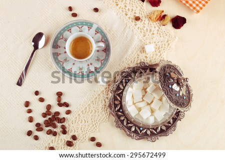Ristretto cup on the table. Espresso, teaspoon, sugar bowl with refined sugar on the table. Scattered coffee beans, rose petals and a cup of coffee. Strong coffee. Breakfast. Cafeteria and restaurant. - stock photo