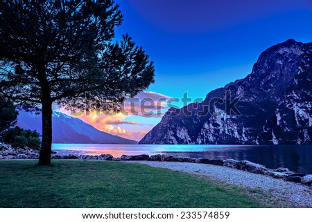 Riva del Garda town and Garda lake by night, Italy - stock photo