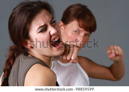rivalry girls - brutal face punch over grey background - stock photo