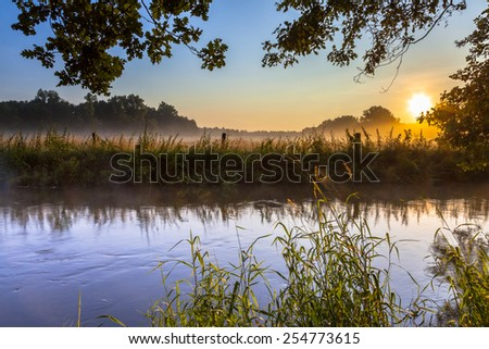 River and bank of the Dinkel in Twente on an early summer morning with haze over the countryside in the Netherlands - stock photo