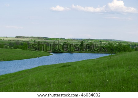 River and green field with blue sky and wood
