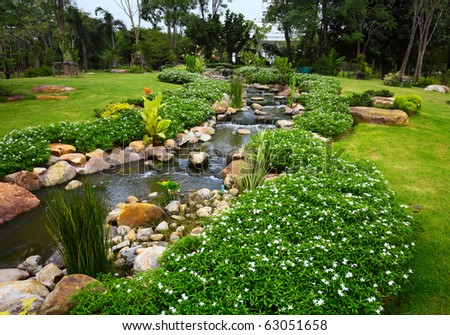River and green grass on meadow in park - stock photo
