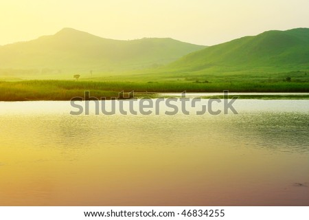 River and mountains with green grass under sunset light - stock photo