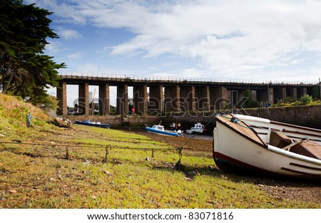 River bank in Cornwall during ebb or low tide. Boats moored on mud with viaduct or bridge in background - stock photo