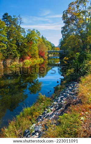 River bank in early autumn. A Bridge in the back. Water reflecting colorful trees. - stock photo