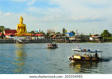 River boats crossing the Chao Phraya river in Bangkok, Thailand,with a giant golden buddha and thai houses in the background - stock photo