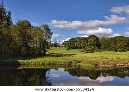 River Brathay at Elterwater in the English Lake District with still water reflecting the clouds - stock photo