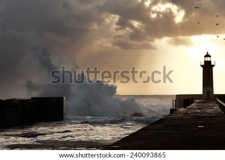 River Douro harbor at sunset with big waves and lightbeams - stock photo