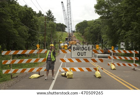 RIVER FALLS,WISCONSIN-AUGUST 18,2016: A highway worker directs traffic around a bridge under construction.