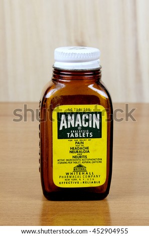 RIVER FALLS,WISCONSIN-JULY 15,2016: A vintage Anacin bottle with wood background. Anacin is a product of Whitehall Pharmacal Company. - stock photo