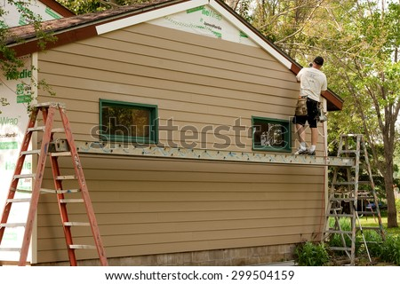 RIVER FALLS,WISCONSIN-JULY 23,2015: A worker installs Hardie Board siding and flashing to an existing structure.