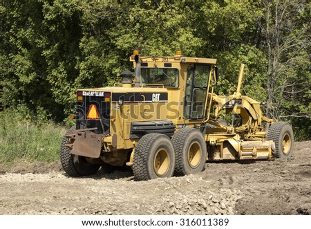 RIVER FALLS,WISCONSIN-SEPTEMBER 13,2015: A Caterpillar brand road grader. Caterpillar is the worlds largest manufacturer of construction and mining equipment. - stock photo