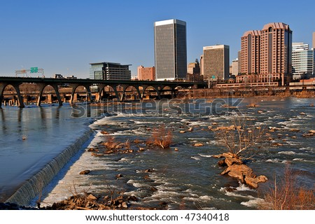 River flowing over rocks in front of a city.  Richmond, Virginia and the James River showing the bridges leading into the city. - stock photo