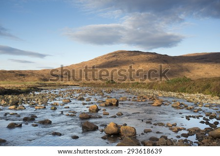 river flowing over rocks overlooking mountains in scotland - stock photo