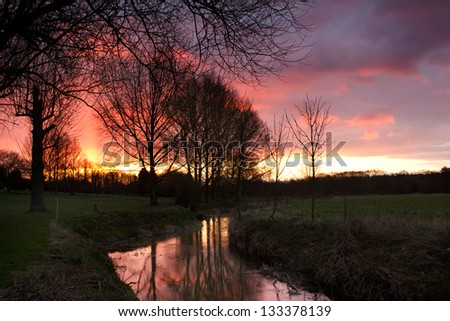 river flowing through an english countryside scene at sunset - stock photo
