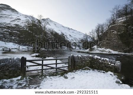 River flowing through snow covered Winter landscape in valley - stock photo