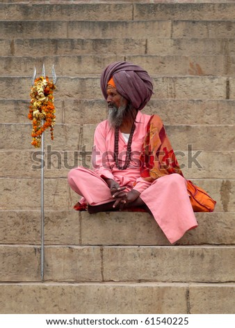 RIVER GANGES, INDIA - CIRCA 2007: Unidentified HolyMan sits on the embankment circa 2007 in India. At the Kumbh Mela Pilgrimage peak, millions of Hindus enter the Ganges to be cleansed of their sins.