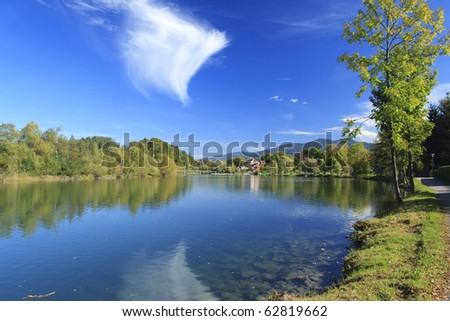 river in autumn with colorful trees and blue sky - stock photo