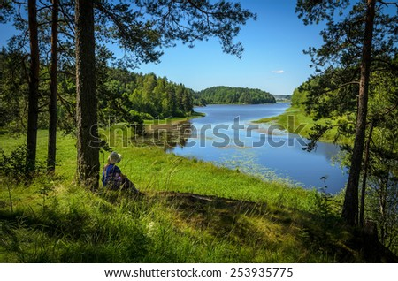 river in grass and forest covered banks - stock photo
